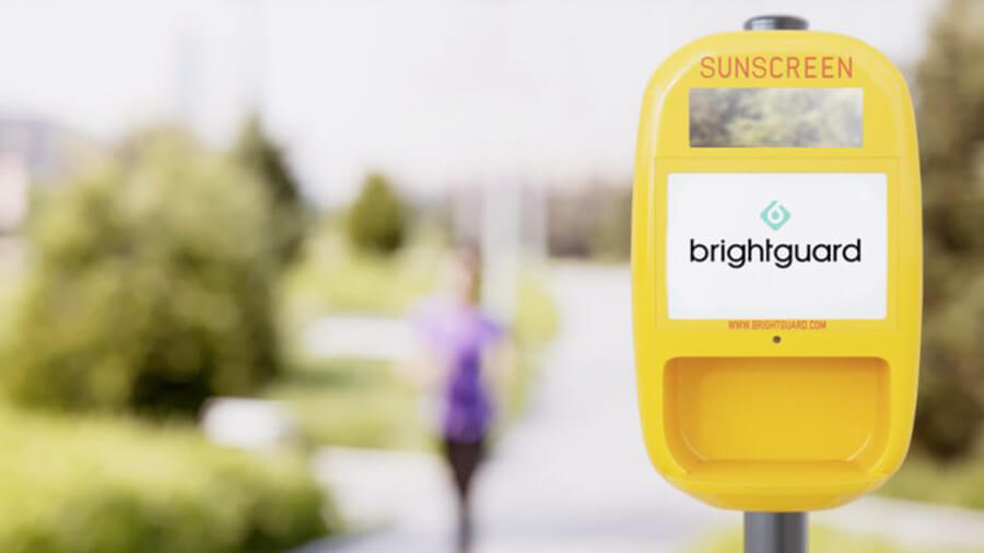 Yellow sunscreen dispenser with woman jogging in the background
